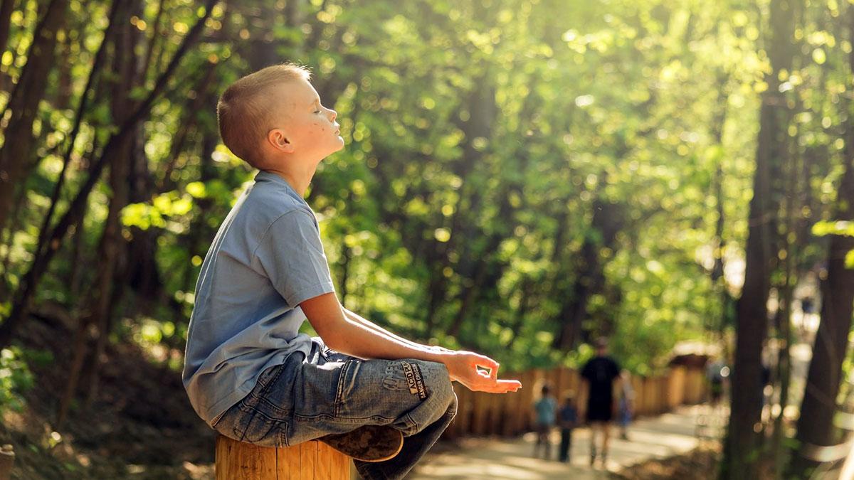 bambino in posizione yoga al sole